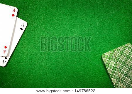 Cards on green felt casino table background. Two aces copy space in center