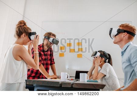 Business team using virtual reality headset in office meeting. Developers meeting with virtual reality simulator around table in creative office. stock photo