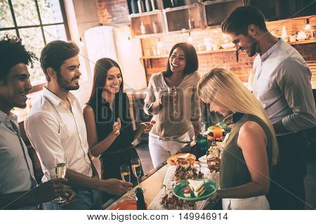 Enjoying home party with best friends. Group of cheerful young people enjoying home party with snacks and drinks while communicating on the kitchen