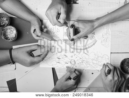 Artists wooden table with paints and colored paper. Creativity and art concept. Hands hold colorful markers and draw kids illustration, top view. Markers in male and female hands draw on white paper stock photo