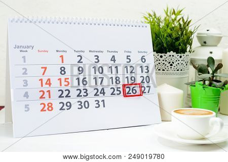 January 26th. Day 26 of month on white calendar, near a cup of coffee and candles stock photo