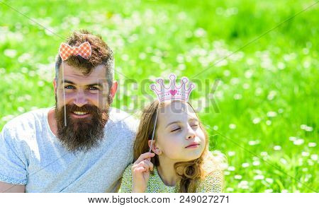 Family spend leisure outdoors, play girlish games. Child and father posing with crown and bow photo booth attributes. Dad and daughter sits on grass at grassplot, green background. Fatherhood concept. stock photo