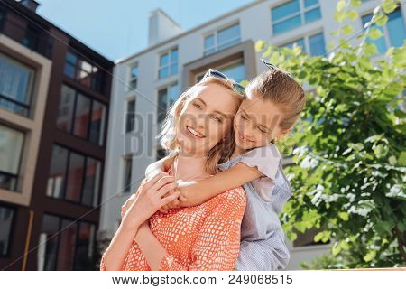 Happy motherhood. Cheerful nice girl smiling while being together with her mother stock photo