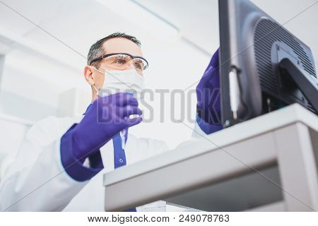 Technological progress. Bioengineer wearing protective glasses while doing scientific experiment stock photo