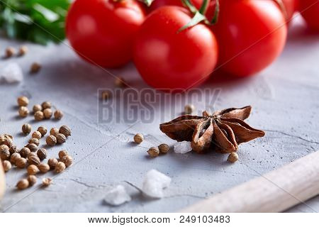 Cherry tomatoes and assorted spices on white textured background, flat lay, close-up, selective focus. Food ingredients and various spices for healthy lifestyle. Cooking and gastronomy concept. stock photo