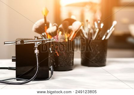Modern airbrush and tools for professional makeup. Make-up products set. Beauty studio background. Cosmetics and brushes on artist workplace stock photo