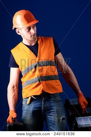 Worker, handyman, repairman, builder on calm face carries bags with professional tools. Man in helmet, hard hat holds toolbox and suitcase with tools, blue background. Professional repairman concept. stock photo