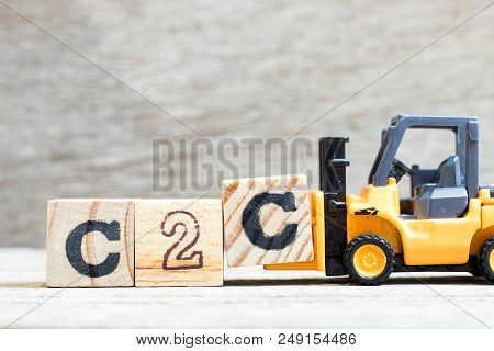 Toy forklift hold letter block C to complete word c2c (Abbreviation of consumer to consumer) on wood background stock photo