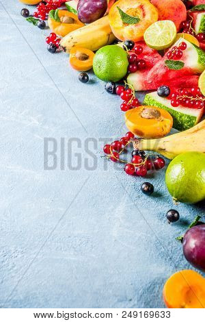 Summer vitamin food concept, various fruit and berries watermelon peach mint plum apricots blueberry currant, creative flat lay on light blue background top view copy space stock photo