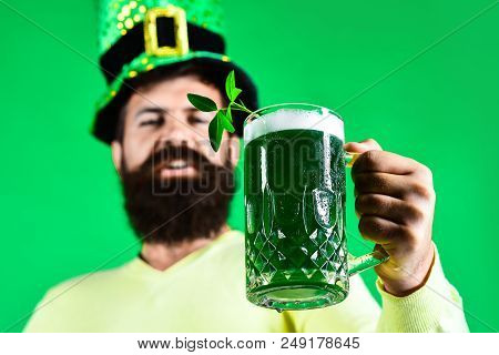 St Patrick's Day. Close up portrait of happy bearded man in leprechaun hat. Clover in glass of beer. Bearded leprechaun. Happy Irish leprechaun with black beard. Bearded man. Selective focus on glass. stock photo