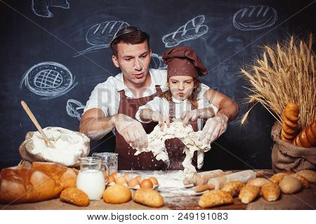 Funny pretending man with little adorable girl having fun while kneading dough and making bread stock photo