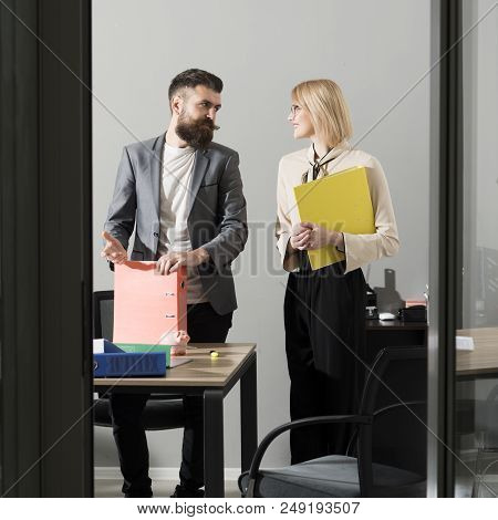 Hipster and woman discuss financial report. Boss talk to secretary in office. Businessman and businesswoman at work process. Communication and cooperation. Savings and handout concept. stock photo