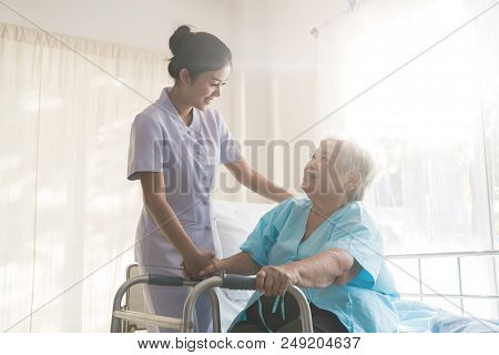 Asian Young Nurse Supporting Elderly Patient Disabled Woman In Using Walker In Hospital. Elderly Pat
