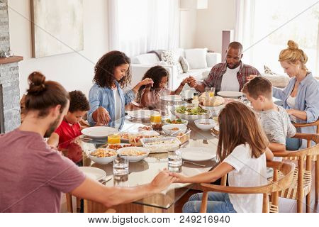 Two Families Praying Before Enjoying Meal At Home Together stock photo