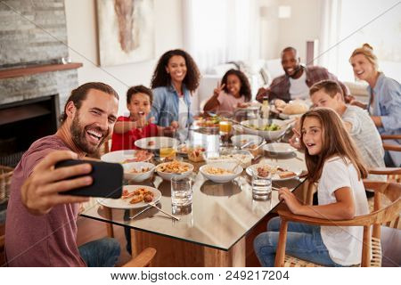 Two Families Taking Selfie As They Enjoy Meal At Home Together stock photo