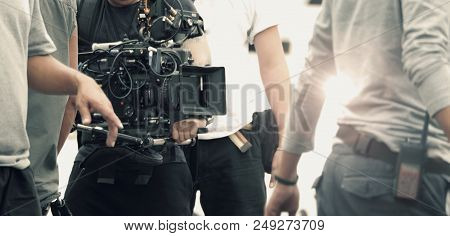 Blurred images of high definition video camera and lens on steady equipment support such as gimbal steady or stabilized shoulder rig and pan tilt shift head tripod for handheld filming a fast moving object in tv commercial production at outdoor location. stock photo