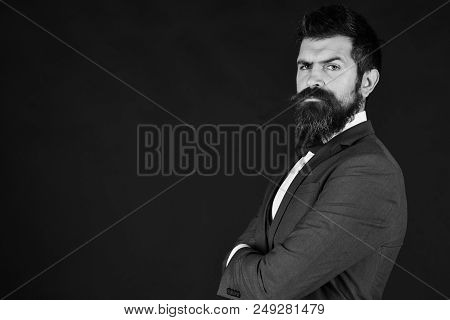 Businessman with confident face with arms crossed. Director or entrepreneur with stylish beard. Man in retro smart suit and tie on brown background, copy space. Entrepreneurship and business concept stock photo