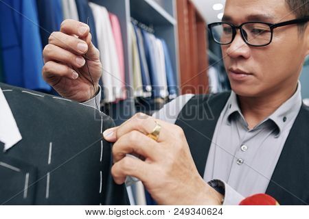 Close-up image of tailor sewing up a sleeve stock photo