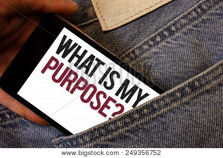 Writing note showing  What Is My Purpose Question. Business photo showcasing Direction Importance Discernment Reflection Human hand bring out cell phone with colorful text jeans back pocket stock photo