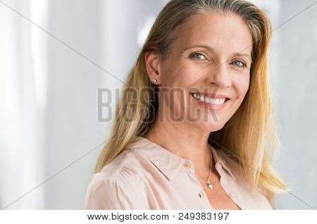 Portrait of mature woman enjoying life after retirement and looking at camera. Closeup face of happy