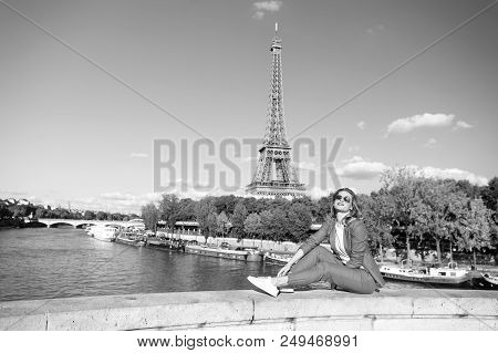 Happy woman sit at river on eiffel tower in paris, france. Woman smile in sunglasses on blue sky. Travelling on summer vacation. Dreaming about paris. Girl with fashion look and sensual beauty. stock photo
