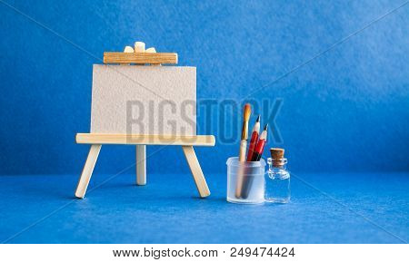 Wooden easel with textured blank paper canvas on blue background. Beautiful art class studio interior, watercolor brushes, pencils in a case, water. Artist's advertising poster mockup. stock photo