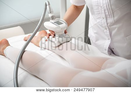 Close up specialist arm keeping appliance while doing anti-fat massage for patient stock photo