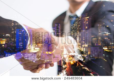 Double exposure concept. Investor business handshake with city night. Businessman shaking hands using as business partnership success concept, Teamwork concept, Investment, Growth. stock photo