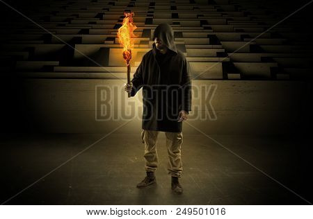 Ugly, aberrant man coming out from the labyrinth with burning flambeau on his hand stock photo
