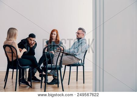 Counselor and teenagers with problems sitting on black chairs during therapy stock photo