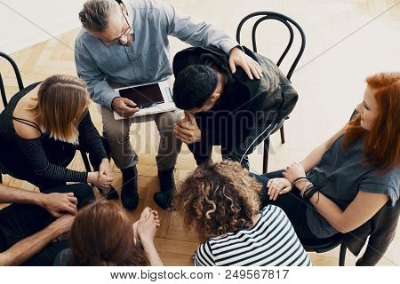 High angle on teenagers with alcohol addiction supporting each other during therapy stock photo