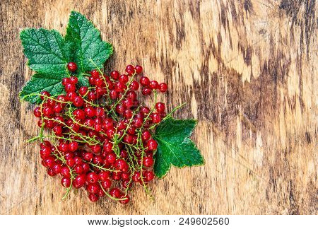 Ripe red currants on a wooden board. Fresh wet currant. Red currant with drops. Old wooden background and red berries. Copy space stock photo