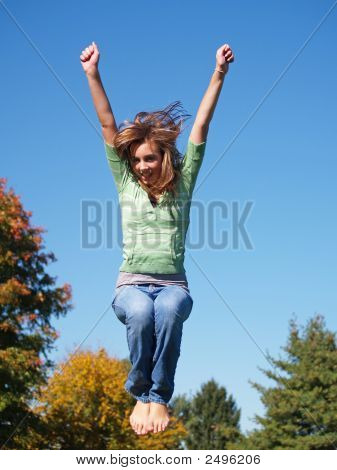 A teenage girl jumping in the air on a sunny day. stock photo