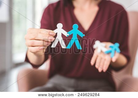 Stay connected. Professional psychologist showing two toy stickmen holding hands while giving an example of harmonious relationships stock photo