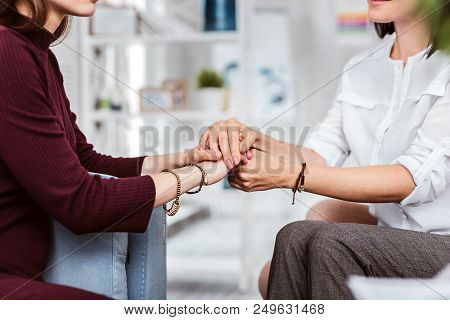 Psychological support. Reliable psychologist sitting opposite the young patient and gently holding her hands while comforting her stock photo