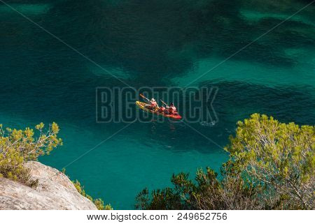 Two adults paddling with baby on board in the colorful Hawaiian sea of Menorca stock photo