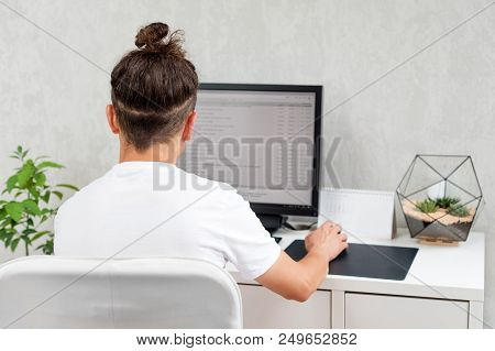 Man working determine workspace lifestyle concept. Young hipster using computer sitting at loft space. Programmer typing data code, working on project in software development company stock photo