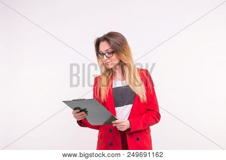 Portrait of young business woman in red jacket with paper clip in hands stock photo