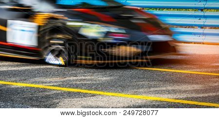 Motor sport car racing on asphalt road with blue fence and yellow line traffic sign. Car with fast speed driving and motion blurred. Black racing car with red and yellow stripes. Car on racetrack. stock photo