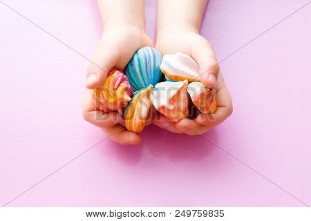 Children's hands hold a handful of colorful little meringue cakes. Hands on a pink pastel background. Appetizing meringues. View from above. stock photo