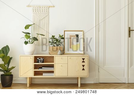 Poster above yellow wooden armchair at table in retro living room interior with window. Real photo stock photo