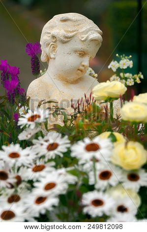 LITTLE ANGEL IN A FLOWER GARDEN. Sculpture of a cute little angel in a garden with assortment of flower varieties. stock photo