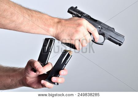 Man reloading pistol gun after shooting isolated stock photo