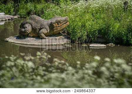 Dinosaur sculpture on the shore of a small pond in the Crystal Palace Park in London stock photo