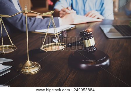 business meeting and lawyers. Justice scales, justice hammer and laptop computer with discussing litigation document at the table. Concepts of law, advice, legal services. stock photo