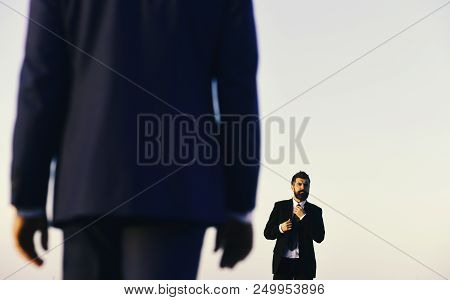 Man with beard and serious face looks forward at colleague in foreground, close up. Managers wear smart suits and ties on blue sky background. Business and success concept. Businessman adjusts tie stock photo
