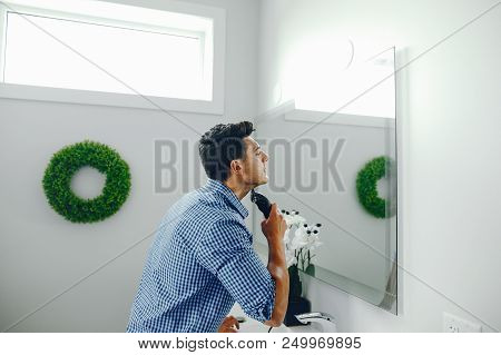 Man with an electric razor. The guy in the bathroom. Male in a bue shirt. stock photo