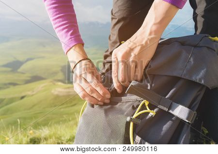 Close-up of women's hands unfasten the buckle on the camp backpack against the background of the valley in the setting sun. Tourism. Tracking. stock photo