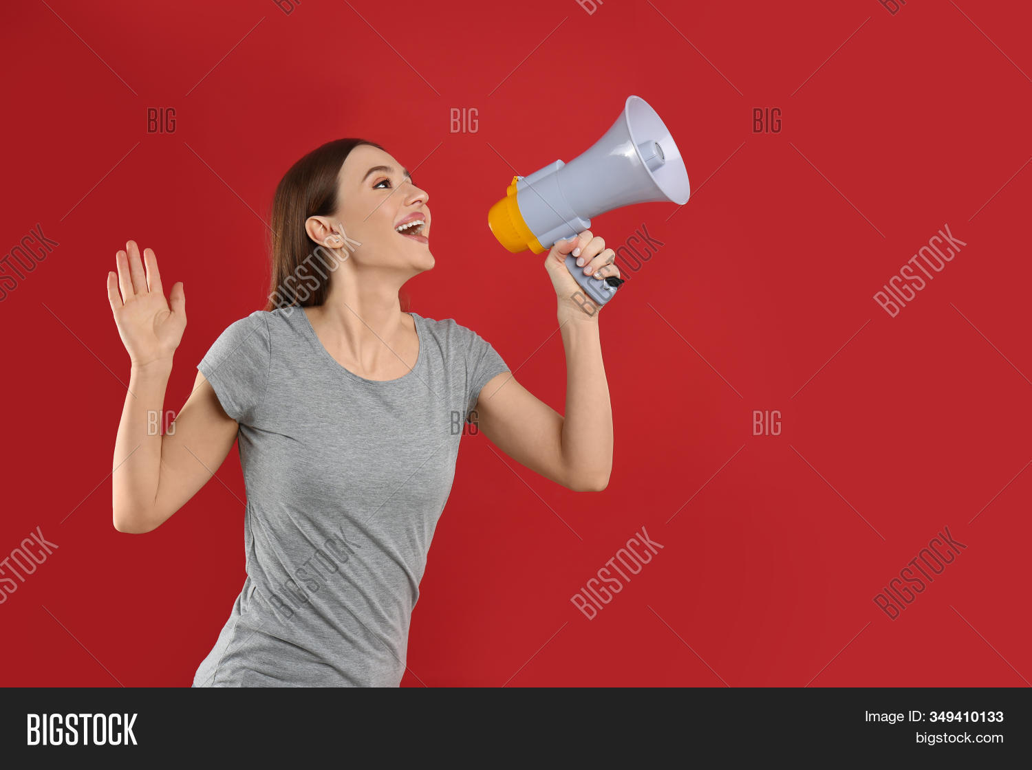 Young woman with megaphone on red background. Space for text