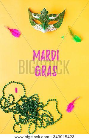 Mardi gras accessories flat lay on bright yellow background, top view, copy space. Woman holding carnival mask and beads. Festival holiday concept overhead stock photo